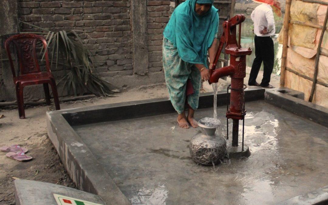Femme qui prend de l'eau au puits